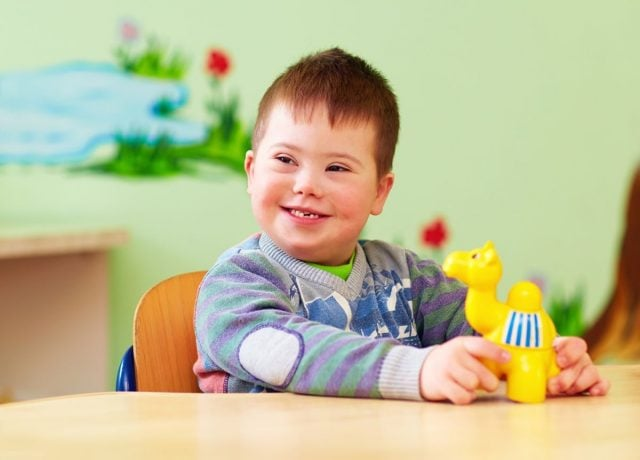 Child with developmental disabilities sits at table with toy