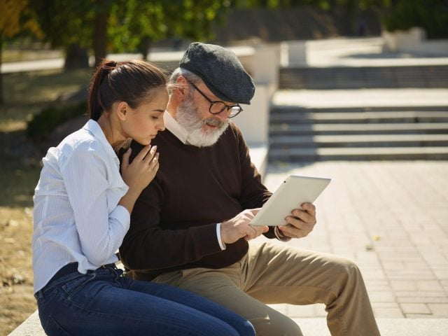 Woman and man in park looking at tablet